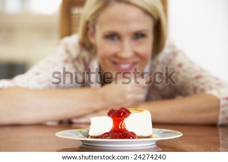 Mid Adult Woman Looking At Cheesecake - stock photo