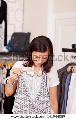 Mid adult woman looking at dress in clothing store - stock photo