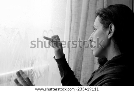 mid adult woman looking out of the window - stock photo