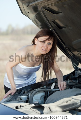 Mid adult woman looking under the car hood