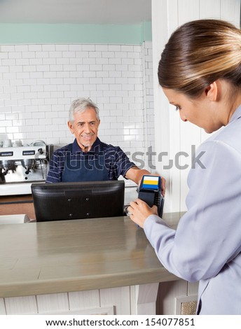 Mid adult woman making payment through mobilephone while senior cashier holding electronic reader at counter - stock photo