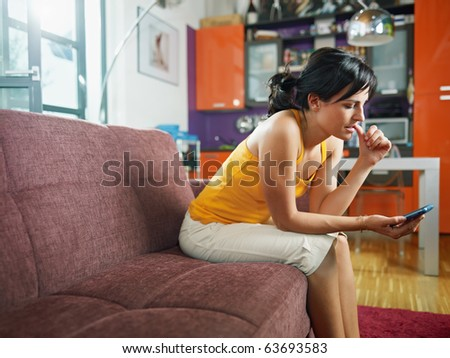 mid adult woman on sofa staring at her mobile phone and biting nails. Horizontal shape, full length, copy space - stock photo