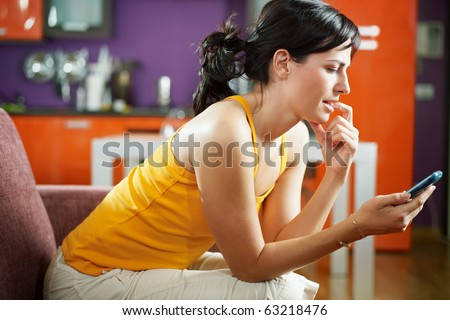 mid adult woman on sofa staring at her mobile phone and biting nails. Horizontal shape, waist up, copy space - stock photo