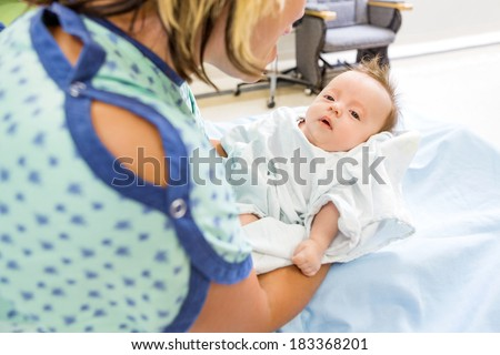Mid adult woman playing with cute newborn babygirl in hospital room - stock photo