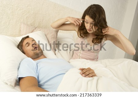 Mid adult woman putting fingers in her ears and a mid adult man sleeping beside her