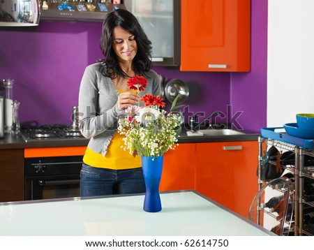mid adult woman putting gerbera in blue pot. Horizontal shape, three quarter length - stock photo