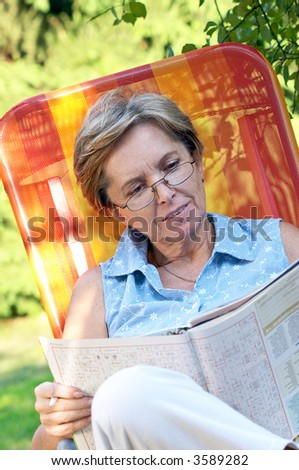 Mid adult woman reading magazine - stock photo