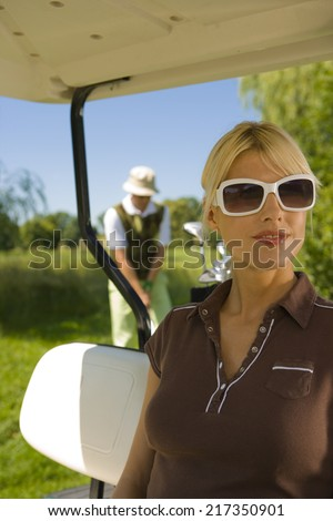 Mid adult woman sitting in a golf cart with a mid adult man playing golf in the background - stock photo