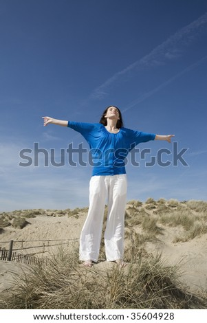 Mid adult woman standing with her arms open on the beach