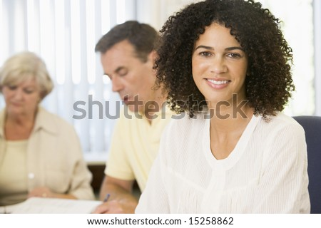 Mid adult woman studying with other adult students - stock photo