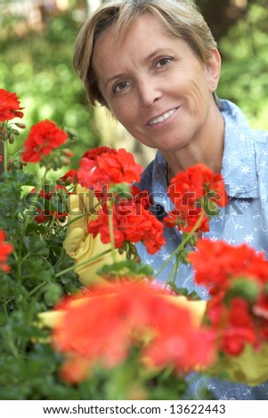 Mid adult woman taking care of flowers - stock photo