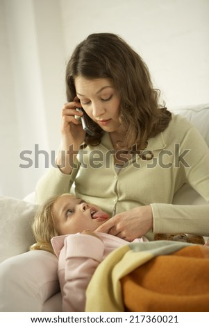 Mid adult woman talking on a mobile phone with her daughter showing her tongue