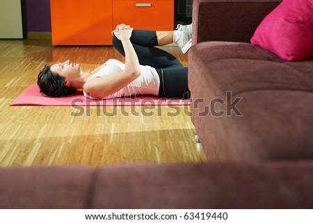 mid adult woman training abdominals at home. Horizontal shape, three quarter length, side view, copy space - stock photo