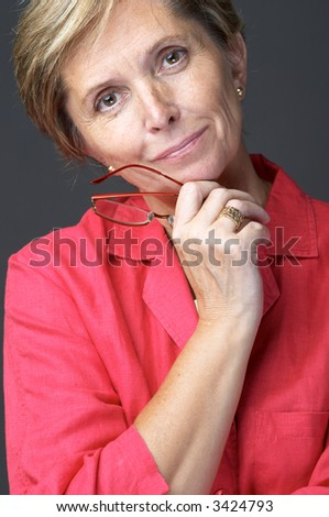 Mid adult woman wearing red shirt looking at the camera, portrait. - stock photo