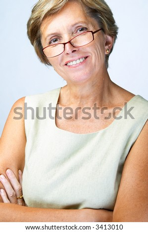 Mid adult woman with arms crossed looks into camera and smiles, studio shot. - stock photo