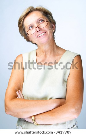 Mid adult woman with her arms crossed looking up - stock photo