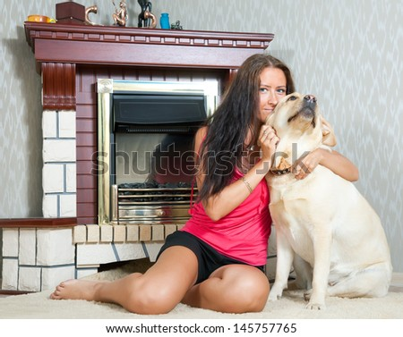 mid adult woman with  Labrador retriever in home interior - stock photo