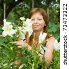 Mid adult woman with lily in her garden - stock photo