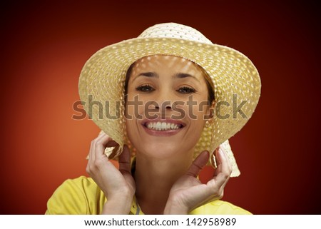 mid adult woman with straw hat smiling and looking at camera on red background - stock photo
