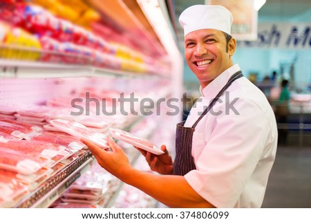 mid age butcher organizing meat products in butchery - stock photo