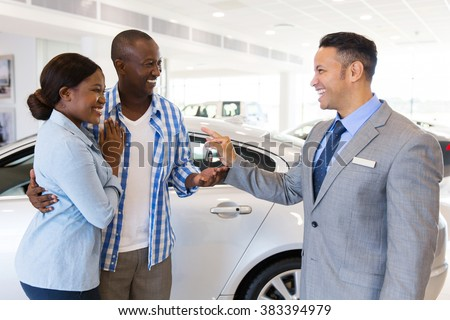 mid age car salesman handing over new car key to african couple in car showroom - stock photo