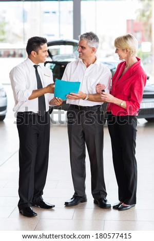 mid age couple buying a new car at dealership - stock photo