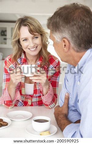 Mid age couple having coffee at home - stock photo