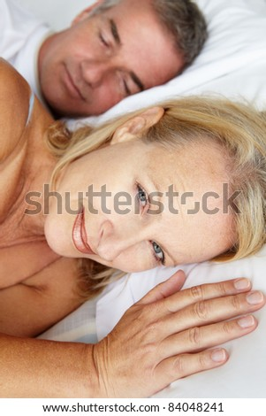 Mid age couple in bed woman awake - stock photo