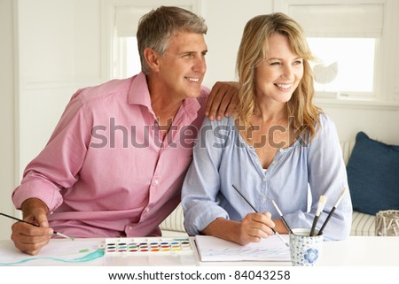 Mid age couple painting with watercolors - stock photo