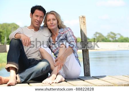 mid age couple seated on a pontoon near a lake - stock photo