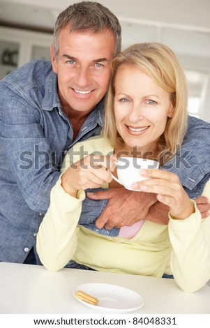 Mid age couple with coffee at home - stock photo