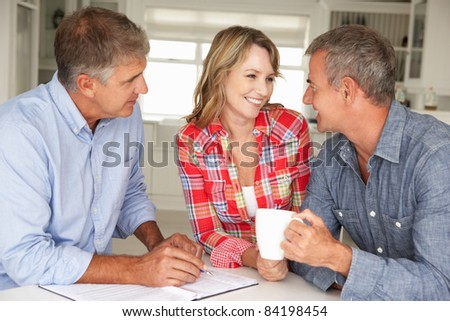Mid age couple with financial advisor at home - stock photo
