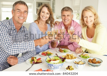 Mid age couples enjoying meal at home - stock photo