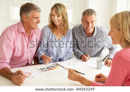 Mid age couples painting with watercolors - stock photo