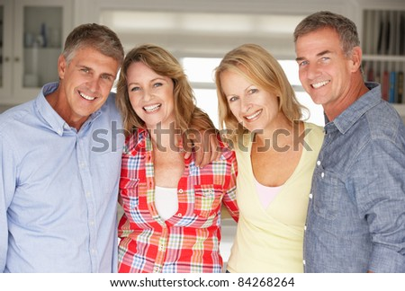 Mid age couples relaxing at home - stock photo