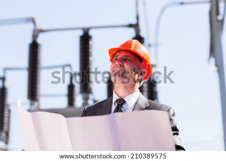 mid age industrial manager working in electric substation - stock photo