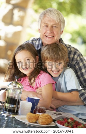 Mid age man and grandchildren eating breakfast outdoors - stock photo