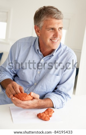 Mid age man clay modelling - stock photo