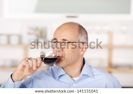 Mid age man drinking red wine at home - stock photo