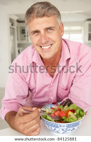 Mid age man eating salad - stock photo