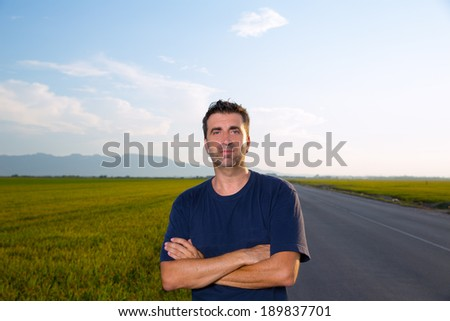 Mid age man in road at meadows posing with crossed arms cereal fields