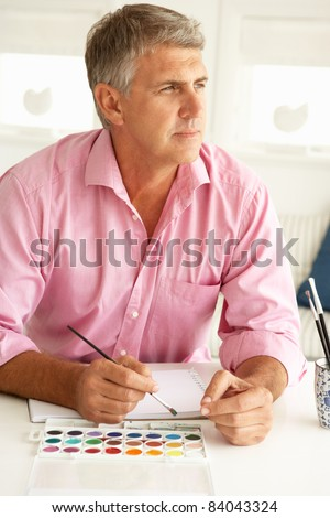 Mid age man painting with watercolors - stock photo