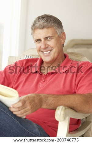 Mid age man reading a book - stock photo
