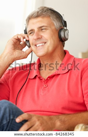 Mid age man wearing headphones - stock photo