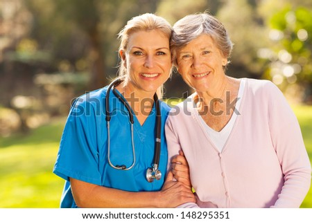 mid age medical nurse and senior patient outdoors - stock photo
