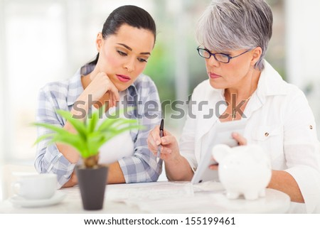 mid age mother helping daughter with her financial at home - stock photo