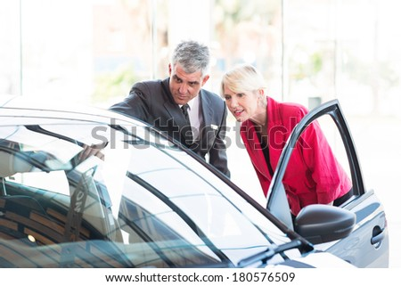 mid age salesman showing new car to potential customer - stock photo