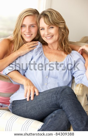 Mid age woman and teenage daughter at home - stock photo