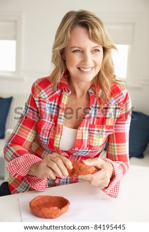 Mid age woman clay modelling - stock photo