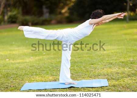 mid age woman doing yoga outdoors - stock photo